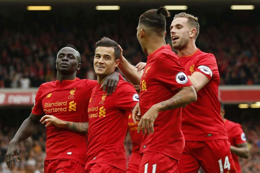 Liverpool's Philippe Coutinho celebrates scoring their fourth goal with team mates.