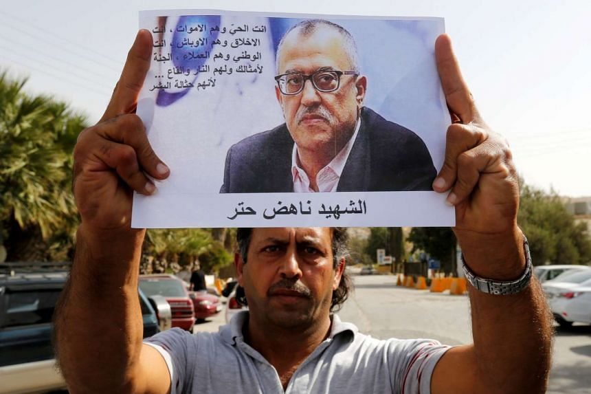A relative of Nahed Hattar holds his picture during a sit-in in Al-Fuheis near Amman, Jordan on Sunday (Sept 25).