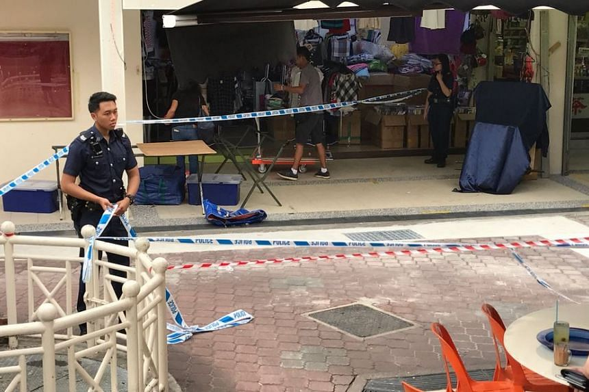 A police officer cordons off an area after a structural feature on the exterior of a HDB block collapsed on Sunday morning in Tampines.