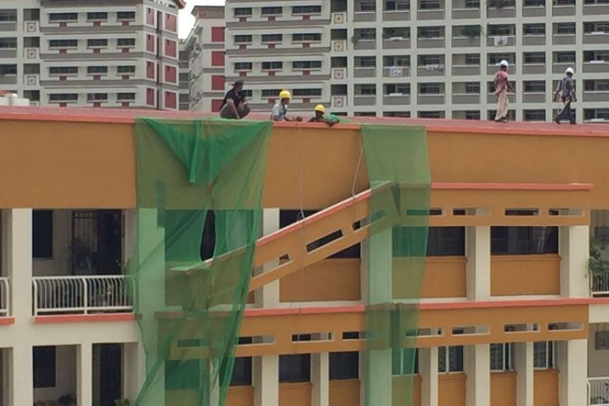 Workers at the site after a structural feature on the exterior of a HDB block collapsed on Sunday morning in Tampines.