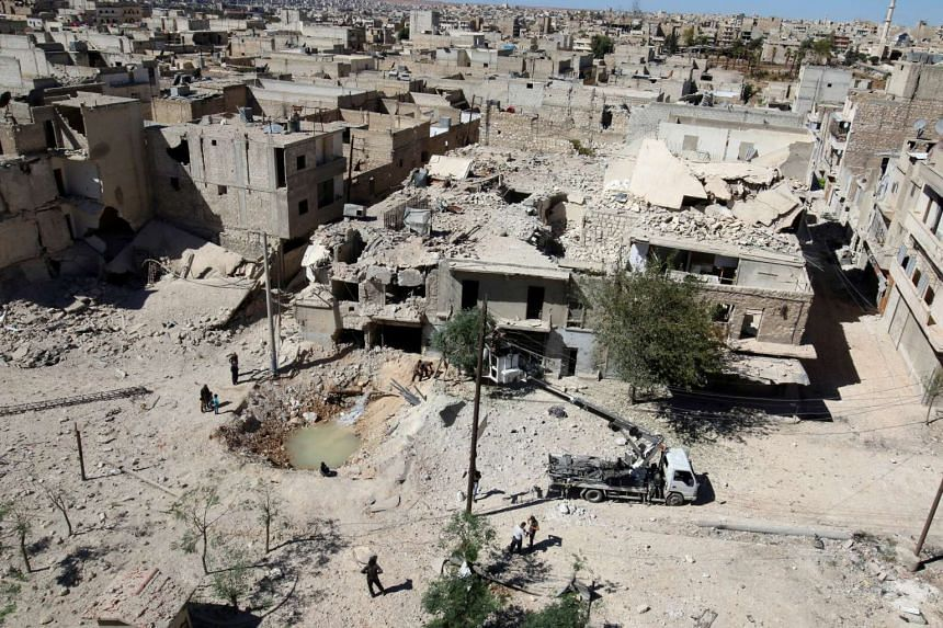 A general view shows a hole in the ground filled with water in a damaged site after air strikes on the rebel held Tariq al-Bab neighbourhood of Aleppo on Sept 24, 2016.