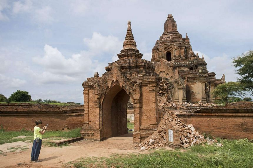 A tourist takes a picture of the damaged ancient Tayoke Pyay Temple in Bagan.