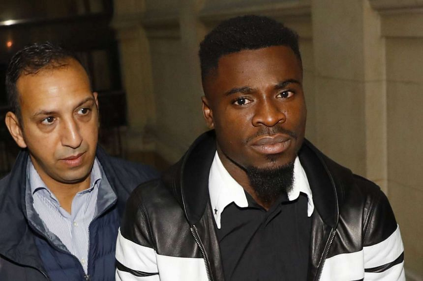 Paris Saint-Germain's defender Serge Aurier (centre) arrives to the Paris courthouse early on Sept 26, 2016 to answer a charge of elbowing a police officer.