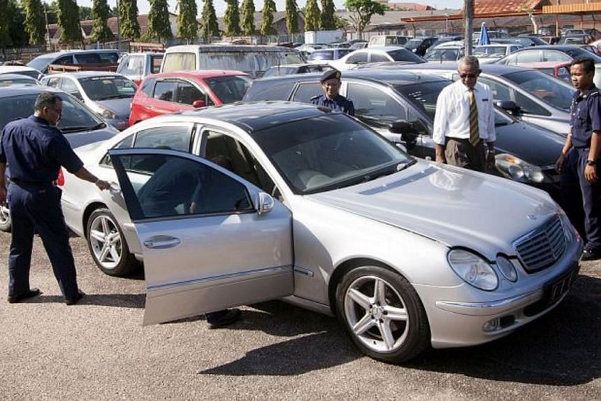 Officers checking the luxury car from Singapore which was confiscated by the authorities.