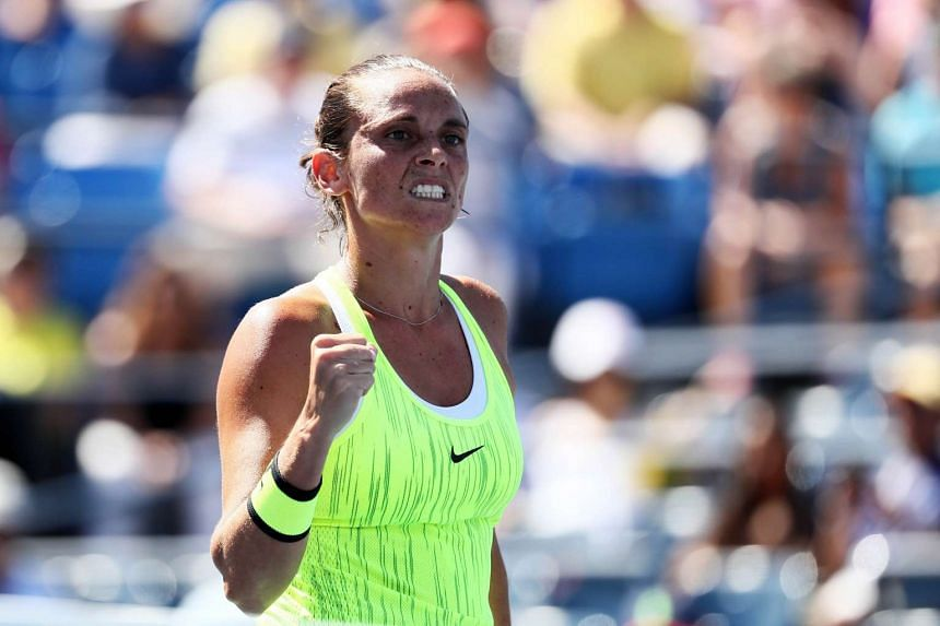 Roberta Vinci celebrates her victory over Olympic tennis women's singles gold medallist Monica Puig in the first round of the WTA Wuhan Open in China on Sunday.