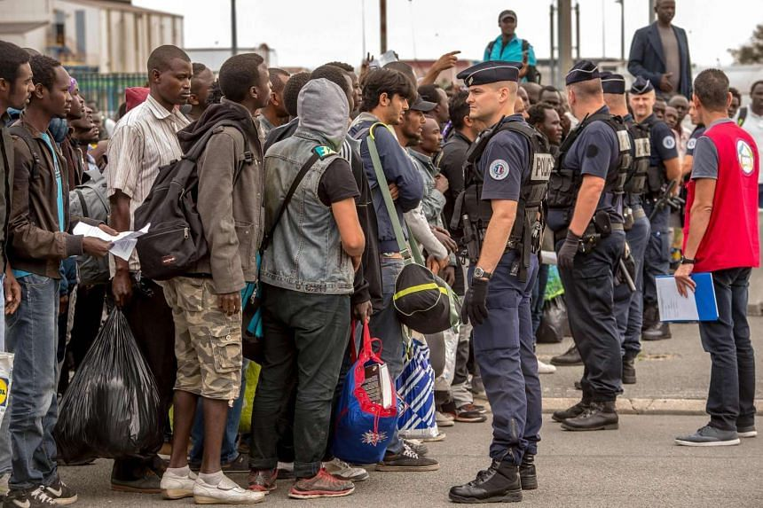 Migrants from the Calais camp wait for a bus under police surveillance, on Sept 13, 2016, as part of a plan to dismantle the camp.