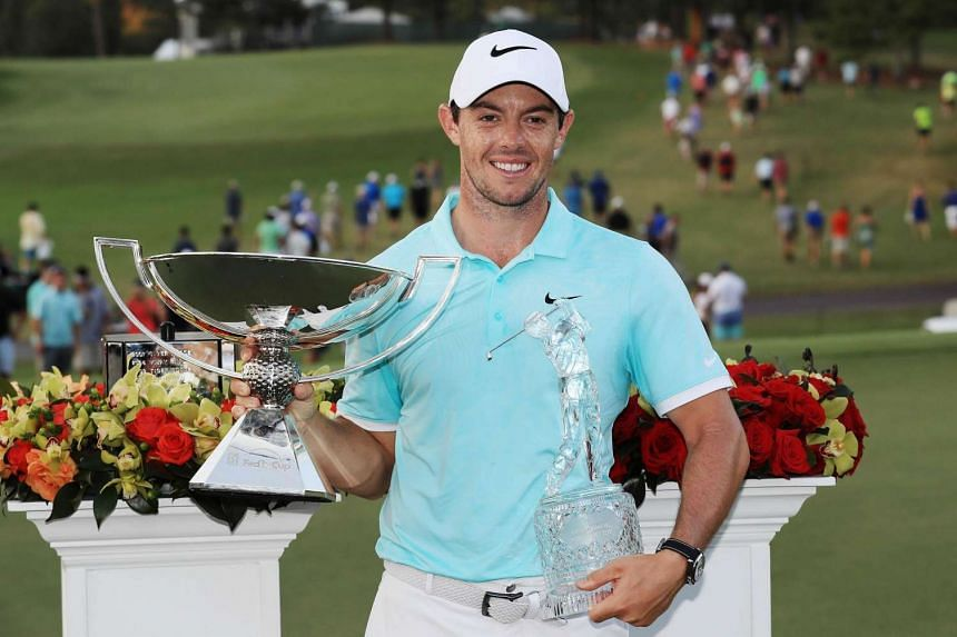 Rory McIlroy of Northern Ireland posing with the FedExCup and TOUR Championship trophies after his victory at the Tour Championship on Sept 25, 2016.