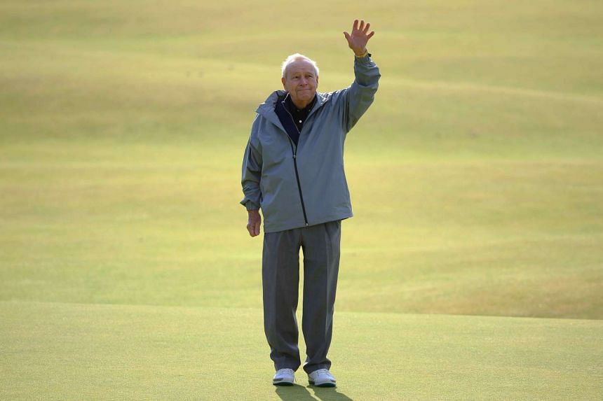 Arnold Palmer waving to the crowd as he stands on the 18th green during the Champion Golfers' Challenge tournament ahead of the British Open golf championship on July 15, 2015.