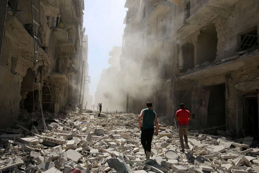 Men inspect the damage after an airstrike on the rebel held al-Qaterji neighbourhood of Aleppo, Syria on Sept 25, 2016.