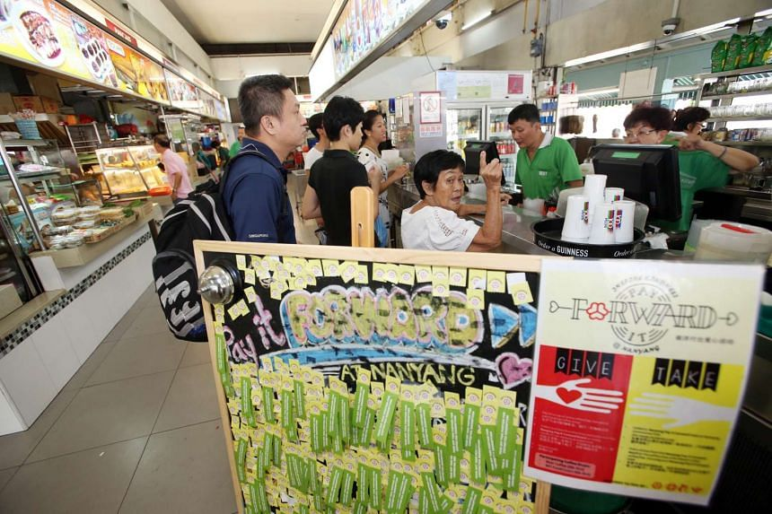 """Residents queueing at a drink stall that participates in a """"Pay It Forward"""" programme at Block 959, Jurong West Street 91."""