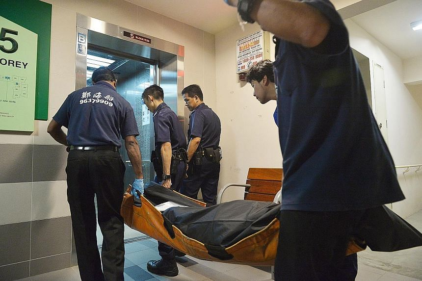 The body of the 61-year-old man, who was reportedly beaten to death, being taken away at Block 152B, Bishan Street 11 early yesterday morning. The 25-year-old man who was arrested in connection to the death is believed to be the younger of the victim