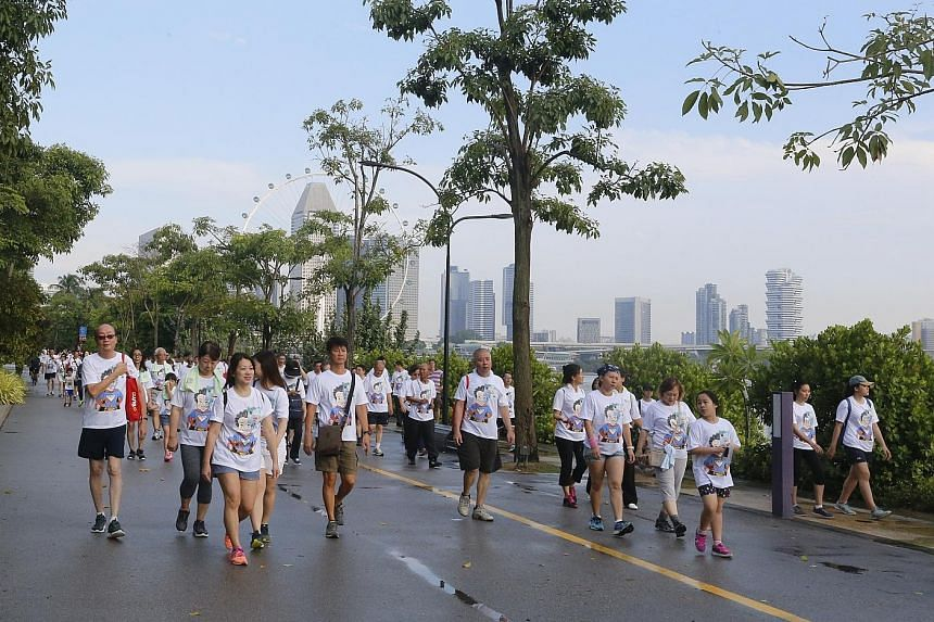 Participants of the 3km walk that took place around Gardens by the Bay and Marina Barrage yesterday. The cabbies were joined by 250 family members, as well as Health Minister Gan Kim Yong, who flagged off the walk.