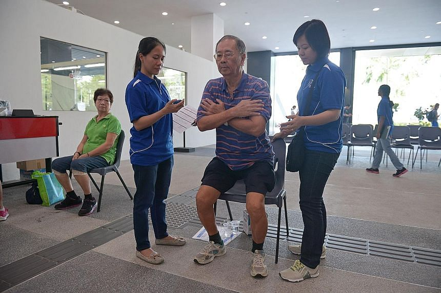 Mr Lim taking the fitness test yesterday at Pasir Ris Sports Complex while his wife, Madam Tan Sai Choo (left), looks on.
