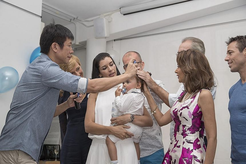 Humanist Society head Tan Tatt Si spraying holy water on one-year-old Julian, who is carried by his mother Andrea Savage, in a godparent naming ceremony last month. Ms Savage and her husband Cameron Richards (extreme right in blue), an Australian cou
