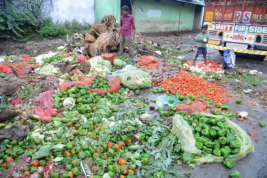 An Indian labourer preparing to collect spoilt vegetables discarded by vendors at a wholesale market, following heavy rain in Hyderabad on Saturday. Rains that have caused heavy flooding around the southern state of Telangana are expected to continue
