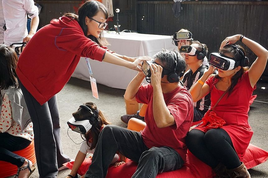 Above: Singaporeans queueing to enter a warehouse at San Francisco's Pier 70, venue of last Saturday's Singapore Day. Left: People posing in a box that simulates the cover of a magazine that celebrates their achievements. Far left: Visitors donning v