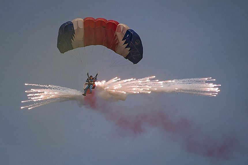 A parachutist releasing fireworks for an aerial display during the second day of the Wonsan Friendship Air Festival yesterday. Just weeks after carrying out its fifth nuclear test, North Korea put on an unprecedented civilian and military air force d