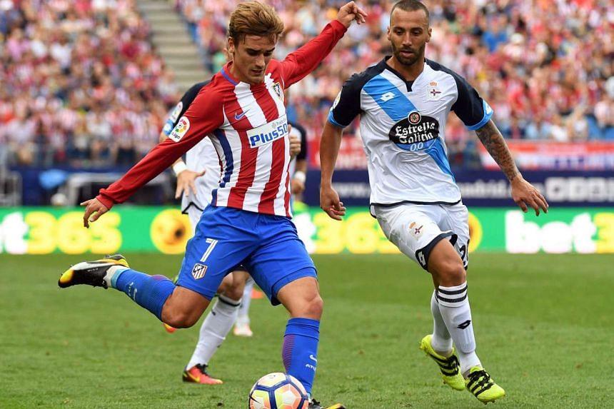 Atletico Madrid forward Antoine Griezmann (left) kicks the ball beside Deportivo midfielder Guilherme on Sunday (Sept 25).