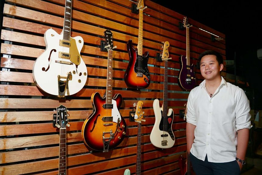 Kuok Meng Ru stands in front of  guitar display at Swee Lee Music in Singapore in July, 2016.
