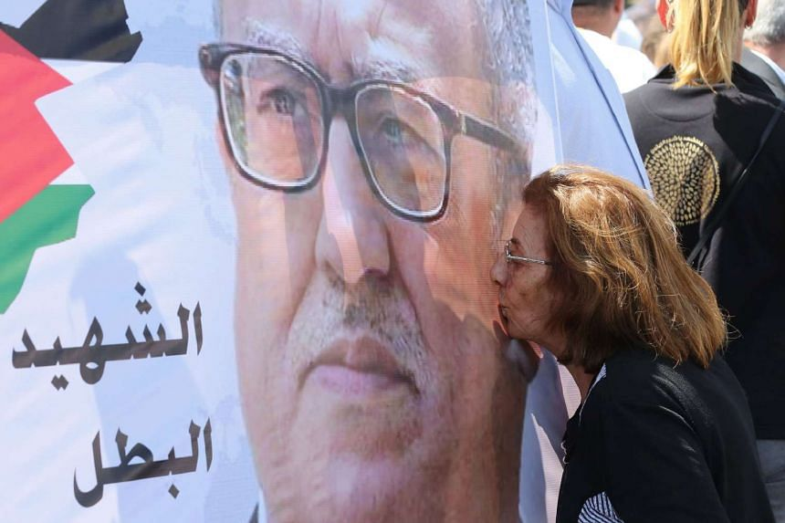 A protester kisses a portrait  Nahed Hattar during a demonstration at  the prime minister's offices on Monday (Sept 26).
