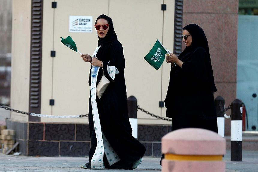 Saudi women hold national flags as they walk on a street during Saudi National Day on Sept 23, 2016.