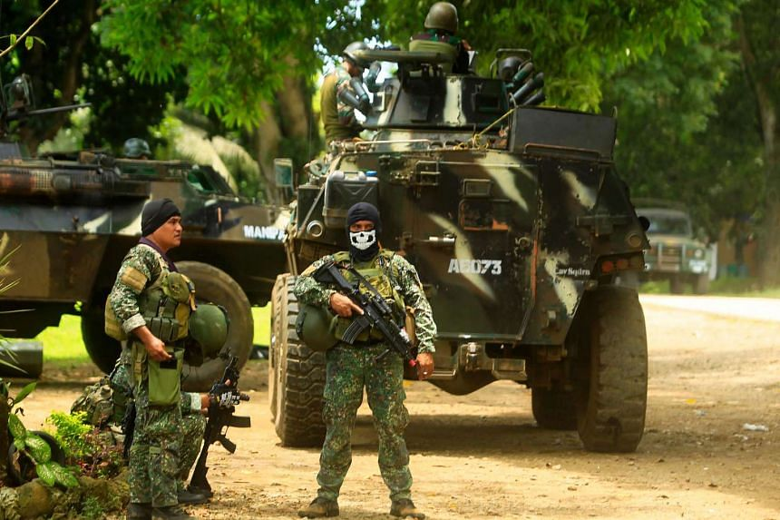 Philippine soldiers standing guard next to an Armored Personnel Carrier as they prepare for an operation against Abu Sayyaf on Sept 5, 2016.