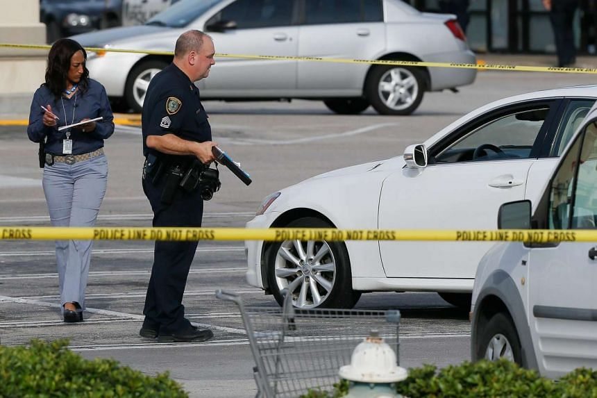 Houston Police investigators photograph a vehicle that received gunshot damage during a scene where nine people were wounded in a strip mall shooting on Sept 26, 2016 in Houston, Texas.
