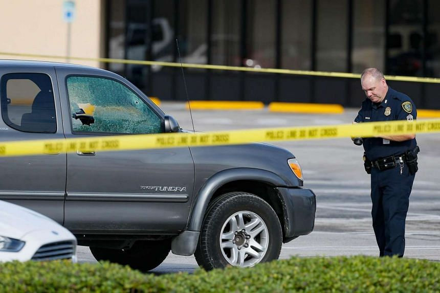 A Houston Police Department investigator photographs a vehicle that received gunshot damage at a scene where nine were wounded in a strip mall shooting on Sept 26, 2016 in Houston, Texas.