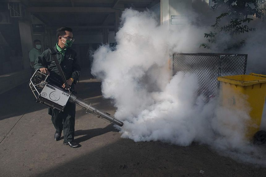 A city worker sprays chemicals with a fumigator to kill mosquitoes in a school in Bangkok on Sept 14, 2016.