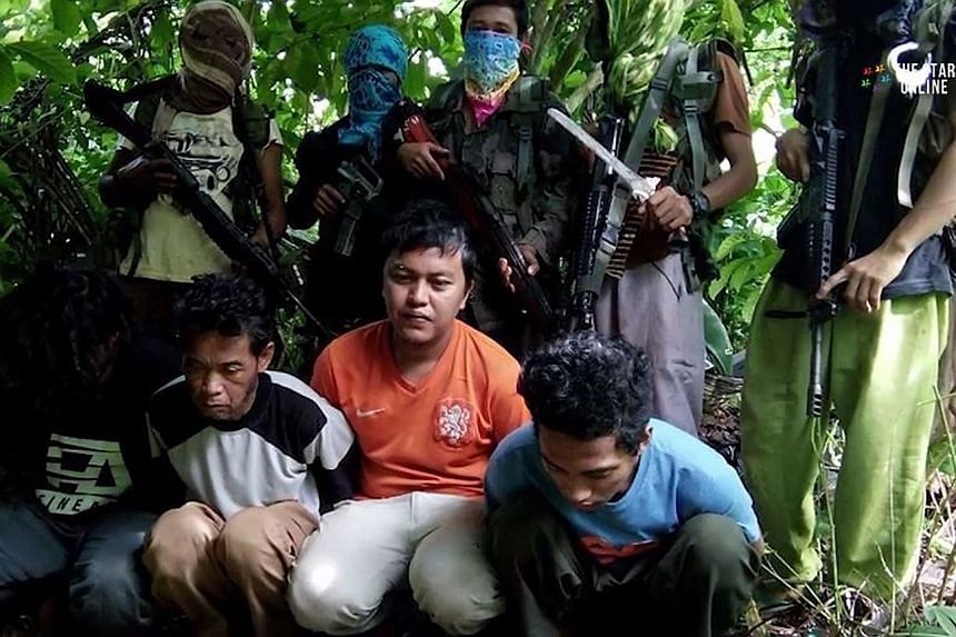 The five kidnapped Malaysians (left and below), surrounded by their Abu Sayyaf captors. They were captured on July 18 off eastern Sabah. A ransom of 100 million pesos (S$2.8 million) has been demanded.