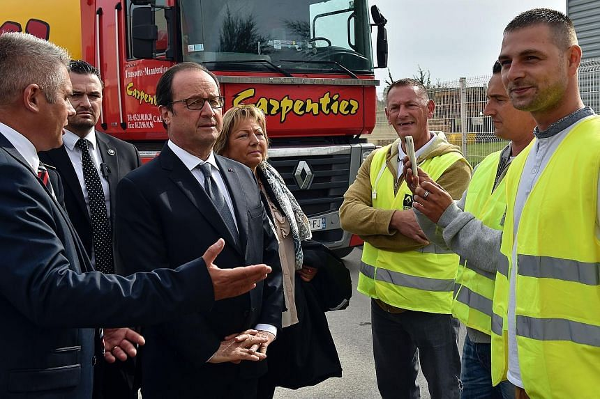 "President Hollande (centre) visiting the French port of Calais, on the outskirts of which lie the sprawling ""Jungle"" camp. The camp, inhabited by thousands desperate to reach Britain, is a symbol of Europe's failure to resolve the migration crisis."