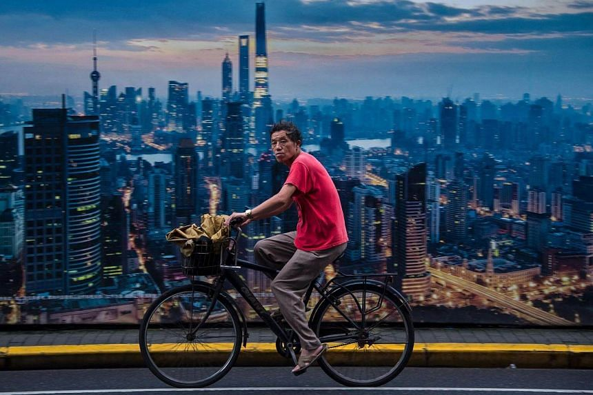 A man cycles past a billboard showing an aerial view of Shanghai.
