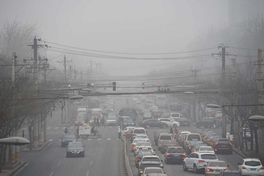 Cars driving beneath a layer of smog in Beijing on Dec 26, 2015.