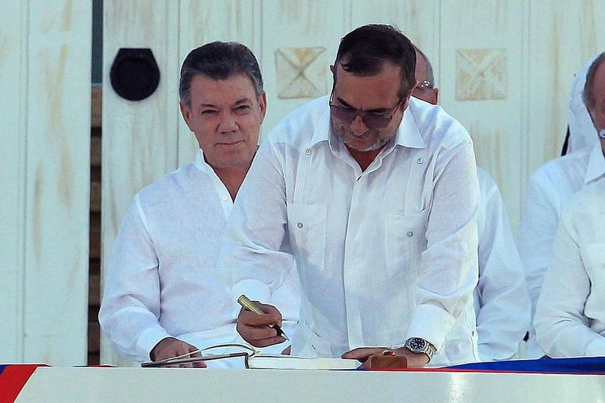 Colombian President Juan Manuel Santos (left) observes Marxist rebel leader Timochenko (right) using a pen made from a bullet to sign an accord ending a half-century war.