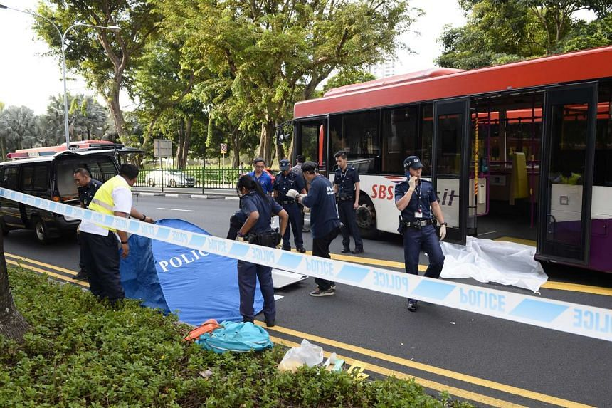 Policemen carrying away the body of a man who was run over and killed by an SBS Transit bus outside Toa Payoh interchange on July 7.
