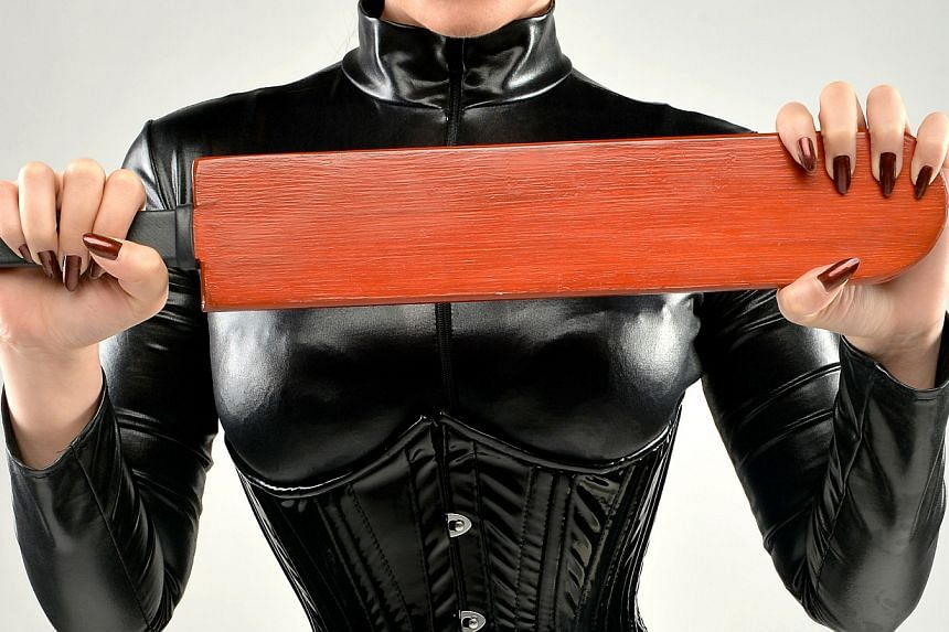 A professional dominatrix in Singapore is dressed to dole out pain to submissive clients.