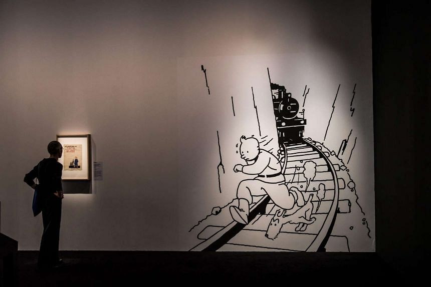 A visitor stands in front of a picture of Tintin on display at the 'HERGE' exhibition in Paris on Monday (Sept 26).