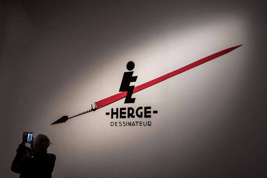 A visitor takes photos at the 'HERGE' exhibition in Paris.
