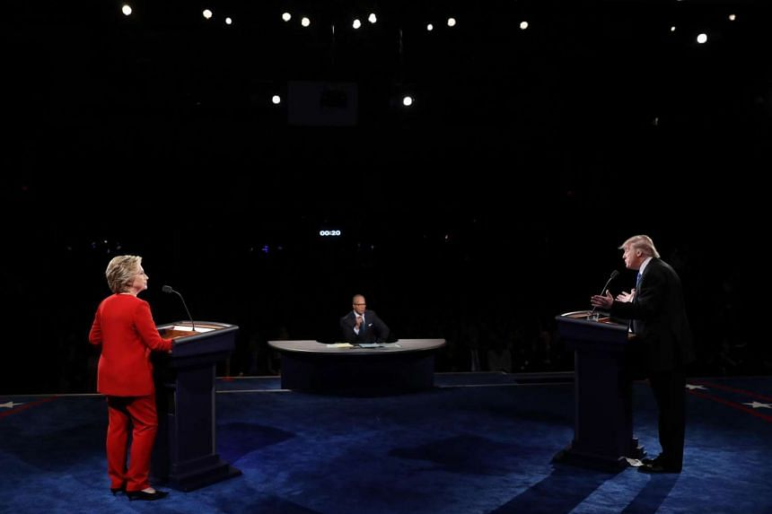 Republican presidential nominee Donald Trump (right) speaks as Democratic presidential nominee Hillary Clinton and moderator Lester Holt listen during the first presidential debate.