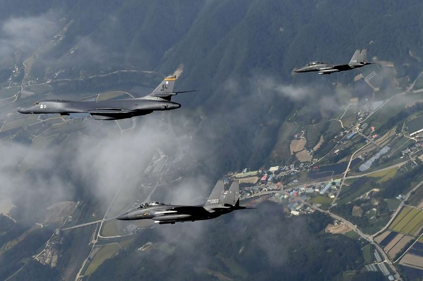 A B-1B 'Lancer' bomber (left) deployed by the US military and two South Korean F-15K fighters flying over Osan Air Base, south of Seoul on Sep 21. The US and South Korea have been conducting joint military exercises in a new show of strength against