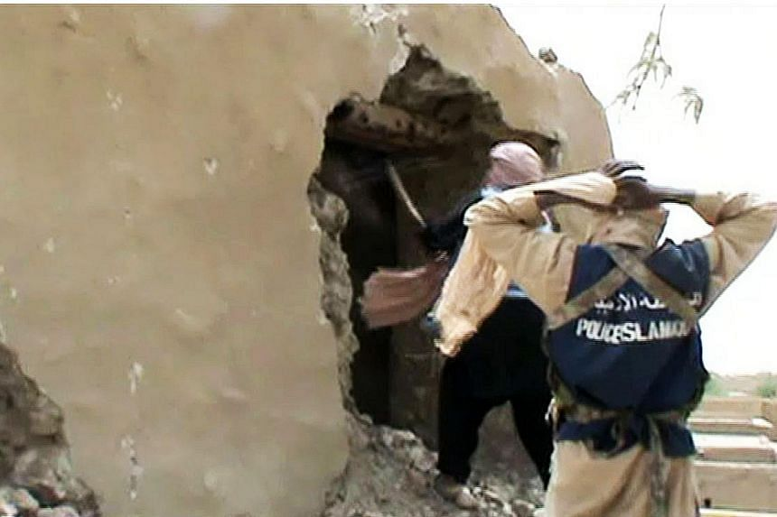 This file image grab photo taken on July 01, 2012 shows Islamist militants destroying an ancient shrine in Timbuktu.