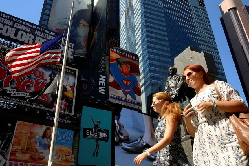 """A video screen shows Republican presidential nominee Donald Trump as """"Super Trump"""" in Times Square area in New York City. The latest figures show that violent crime in the United States rose last year, data that Trump could use against his rival Hill"""