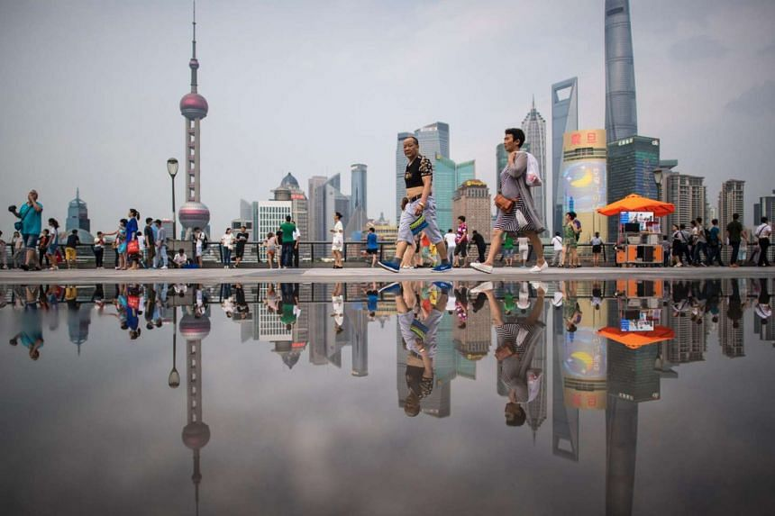 People walking at the Bund overlooking the financial district of Pudong in Shanghai.