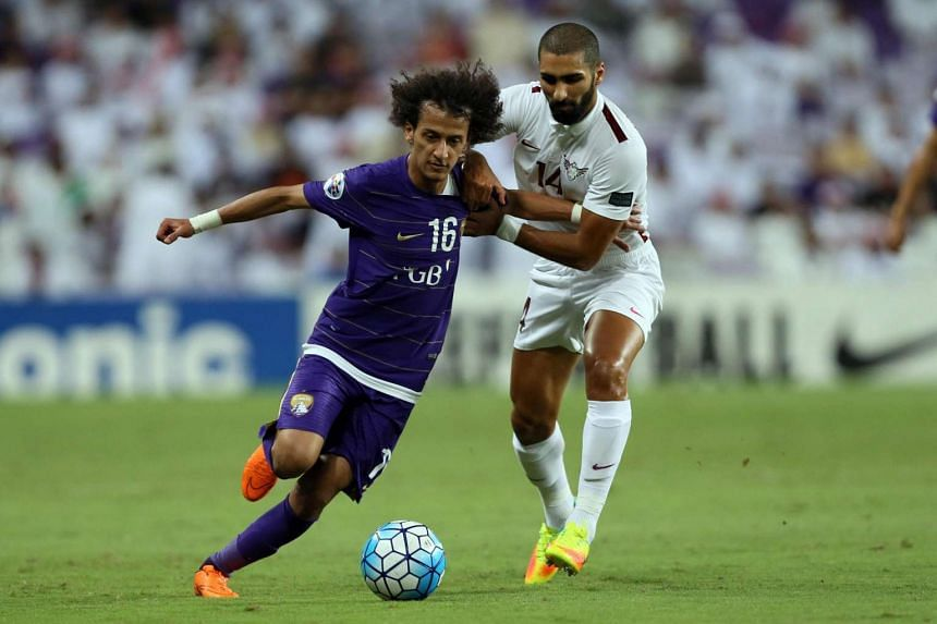 UAE's al-Ain club player Mohamed Abdulrahman Alraqi (left) fights for the ball with Qatar's el Jaish club player Mohd Methnani (right) during a semi-final first leg of the Asian Champions League football at Hazza Bin Zayed Stadium Al-Ain on Sept 27,