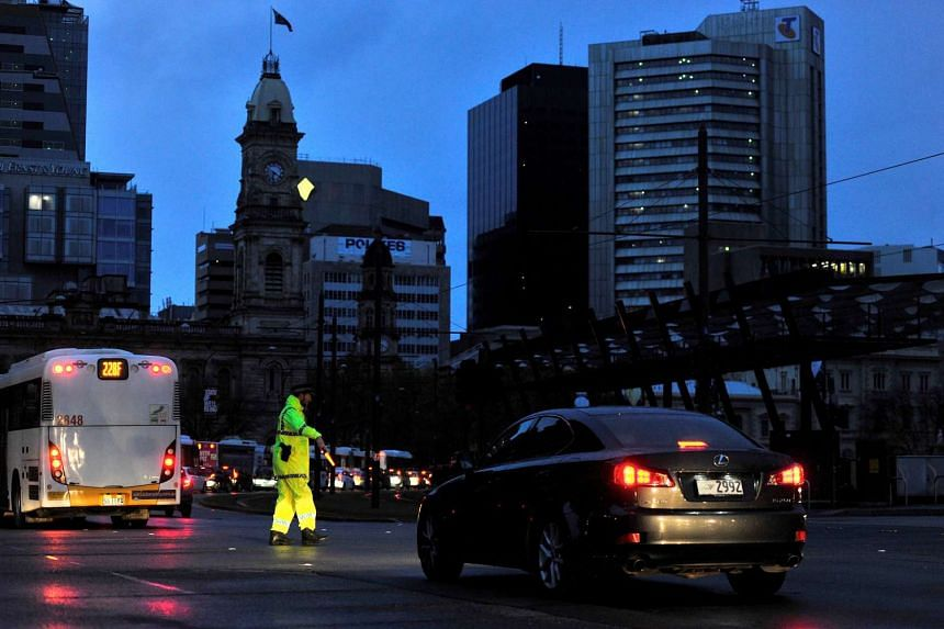Police direct traffic in the central business district of Adelaide after severe storms and thousands of lightning strikes knocked out power to the entire state of South Australia on Sept 28.