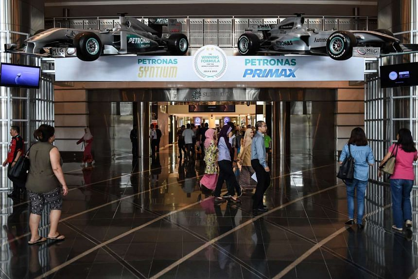 Shoppers walk under replicas of Formula One cars hung on display at a shopping mall in Kuala Lumpur on Sept 27, 2016.