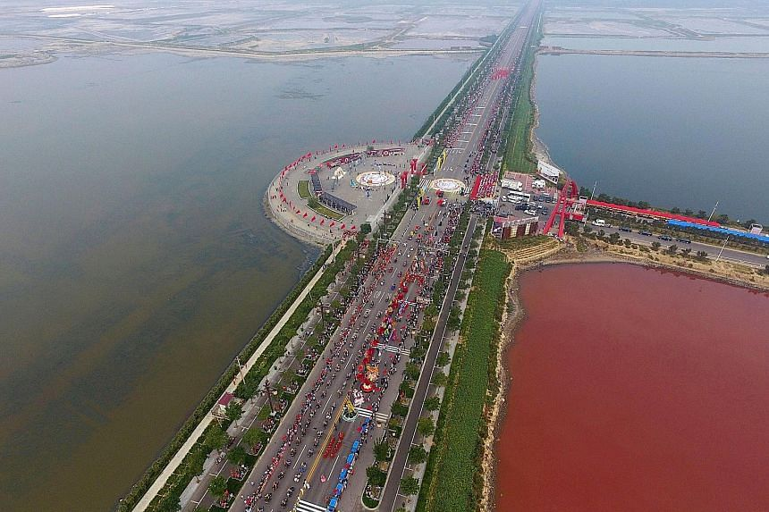The colour of an ancient salt lake in the Chinese city of Yuncheng in Shanxi province has turned to rose pink on one side because of the spread of red-coloured algae called dunaliella salina. Many residents flocked to the area this week to see the ch