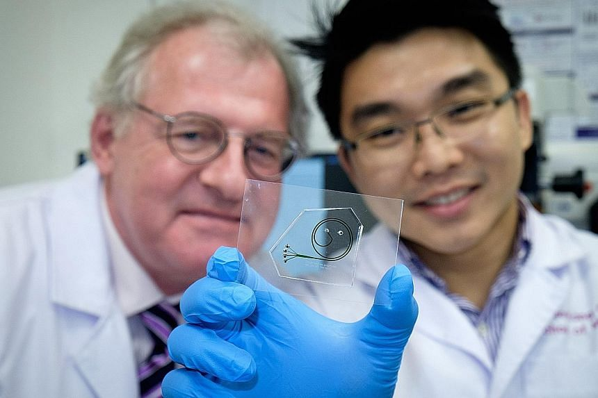 Prof Boehm and Dr Hou with the quick test kit. It contains a chip which extracts white blood cells from a patient's blood sample, and an analyser which doctors can use to observe the cells' movement and function. This helps them to conclude whether t