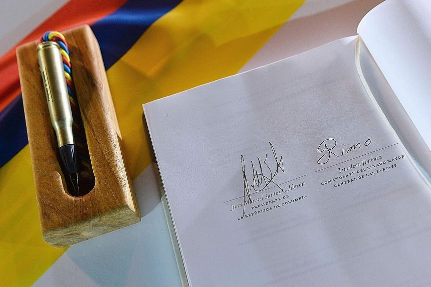 "The peace deal with the signatures of Mr Santos (at right) and Timochenko, and the ""bullet pen"" used to sign it."