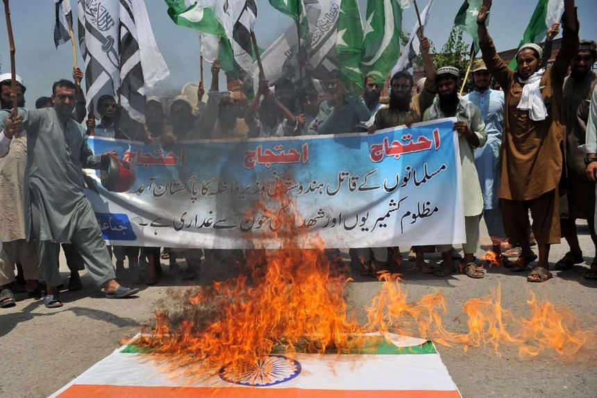 Pakistani activists of the hardline organisation Jamaat-ud-Dawa stand beside a burning Indian flag during a protest against a visit by Indian Home Minister Rajnath Singh in Peshawar on Aug 3, 2016.